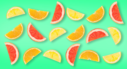 Slices of different citrus fruits on green background