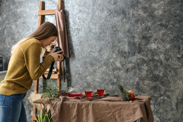 Young woman taking picture of tasty drink in professional studio