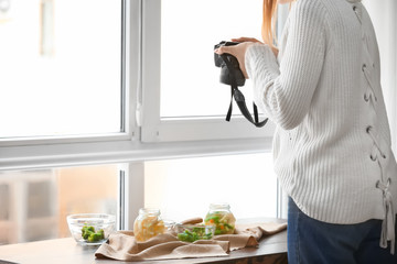 Young woman taking picture of vegetables in professional studio