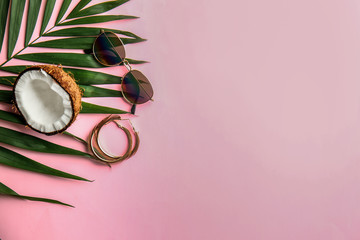 Stylish sunglasses with earrings, palm leaf and coconut on color background