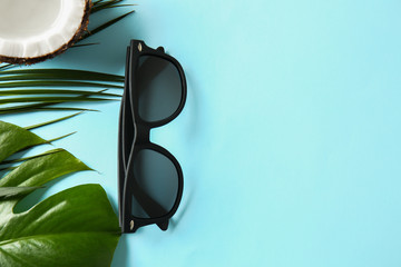 Stylish sunglasses with tropical leaves on color background