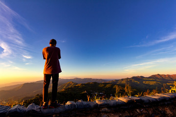 Silhouette of traveler taking photo at top of mountain.