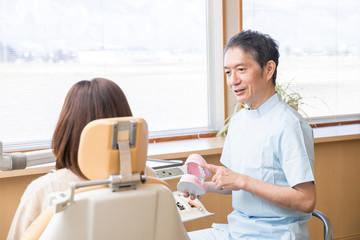 歯医者で説明を受ける女性