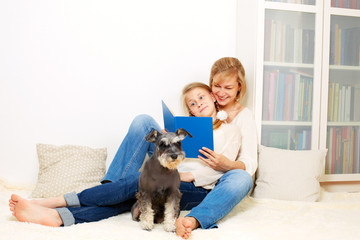 Mother with her 10 years old kid girl reading the book, casual lifestyle photo series. Cozy homely scene.