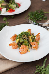 Salad with shrimps on a white plate is on the table.