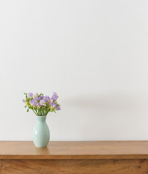 Purple freesia flowers in green vase on wooden table against white wall with copy space (selective focus)