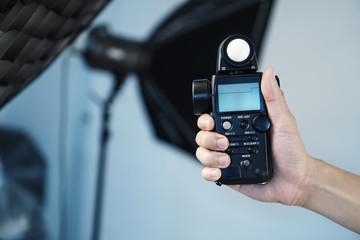 Hand held light meter isolated in studio lights