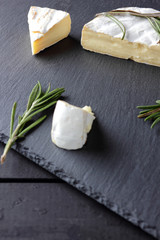 Camembert and rosemary on black stone board. Soft cheese with white mold on black background. Sliced cheese and rosemary branches on slate board. Copy space