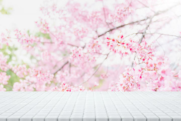Empty white ceramic mosaic table top and blurred sakura flower tree in garden background with vintage filter - can used for display or montage your products.