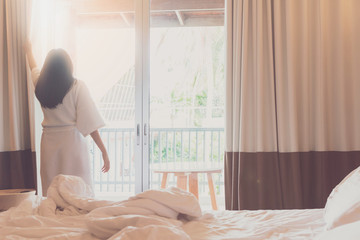 Asian women are staying in a hotel room after wake up on morning. Open the curtain in the room looking to outside view.Concept of traveling and resting happy in good hotel.Vintage tone.