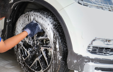 Closeup of front wheel of white car washing, rubbing and cleaning by male worker's hand in sunny day.
