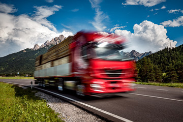 Timber truck rushes down the highway in the background the Alps. Truck Car in motion blur.