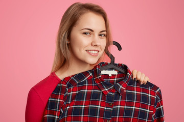 Headshot of smiling pleased European woman with toothy smile, holds checkered shirt on hangers, enjoys shopping during rest day, isolated over pink background. Female shopaholic poses indoor