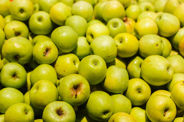 Green apples on a display in a supermarket in bulk