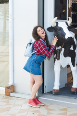 Cheerful young woman with a cow head statue in front of shop