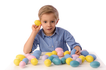 Child and Easter. The boy is playing with Easter eggs. They examine if there are yellow little chicks inside. Preparations for Easter and spring.