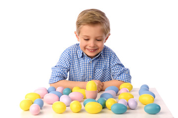 The child is painting eggs for Easter day. Nice, smiling boy sitting at a table with colorful eggs in baskets, yellow chicks. Happy Easter. Isolated on a white.