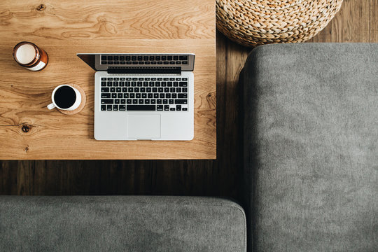 Flat lay of home office desk workspace. Laptop, coffee cup on wooden table, sofa. Top view modern interior design concept.