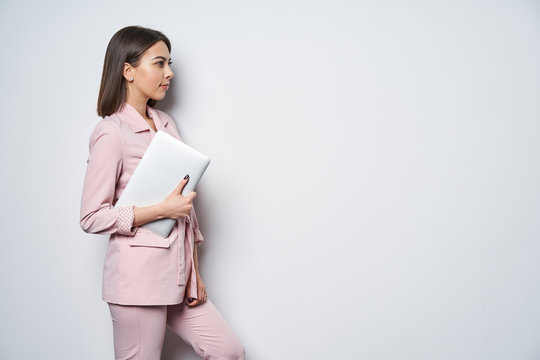 Confident business woman wearing pink suit with laptop underarm