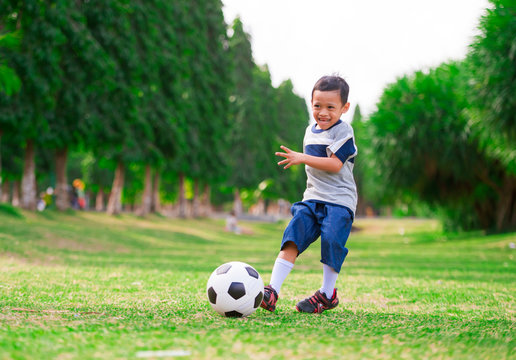 lifestyle portrait at grass city park of 5 years old Asian Indonesian kid playing football happy and excited kicking the ball smiling cheerful in child sport practice education