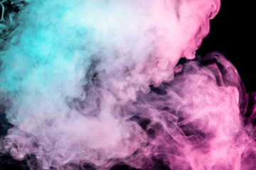 Translucent, thick smoke, illuminated by light against a dark background, divided into three colors: blue, green and purple, burns out, evaporating from a steam of vape.