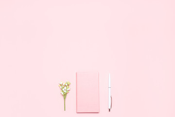 Pink diary,white pen and blooming sprig on pink desk. Minimalistic flat lay composition with copy space for bloggers, designers, magazines etc.