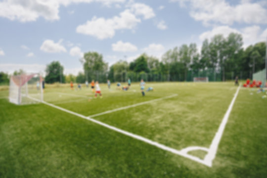Blurred picture of soccer field at school on summer day time. Background image of blurred football pitch. Image for background usage