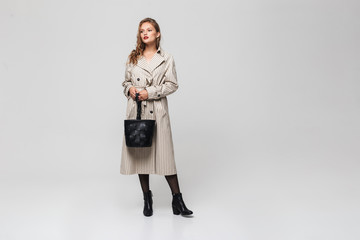 Young beautiful woman with wavy hair in striped coat holding black bag in hands while dreamily looking aside over gray background