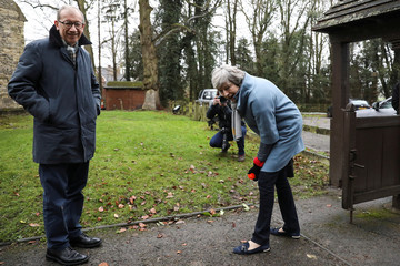 Britain's Prime Minister Theresa May tries to throw a ball for  a dog as she leaves a church near High Wycombe