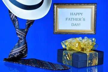 Happy father's day-tie, hat and gift on creative blue background. An annual celebration in honor of the fathers, a place of honor for the popes on this special day.