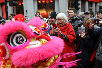Spectators react as performers dressed in traditional dragon costumes take part in the Chinese Lunar New Year parade through central London