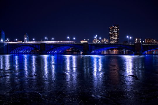 The red T moving across the Longfellow bridge with the Hancock building and frozen Charles river,