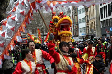 Spectators watch as performers move a traditional Chinese dragon as they take part in the Chinese New Year parade through central London