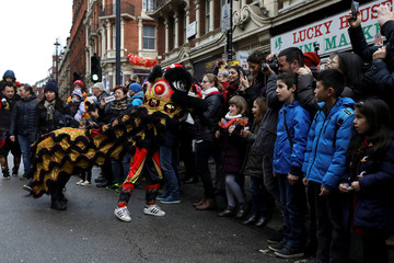 Spectators watch performers dressed in traditional dragon costumes as they take part in the Chinese New Year parade through central London