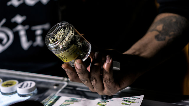 A Vendor Showing Off A Jar Of Cannabis Flowers