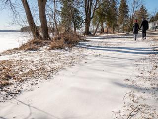 Couple walking along snowy path near a lake in winter