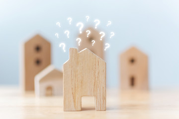 Real estate developer and managing property investment concept. Selective focus wooden houses with question mark on table