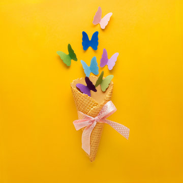 Eat and fly / Creative concept photo of ice cream waffle cone with paper butterflies on yellow background.