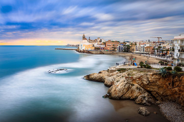 Sitges is known for its beaches, nightspots, and historical sites. The beach seen here is playa san sebastian and the church is a real landmark, san bartolome iglesia.