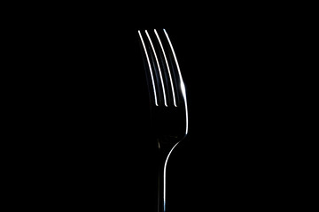 Fork on a black background with light from the side