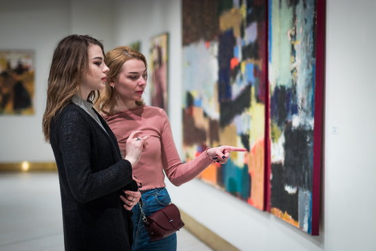 two girls discuss paintings in Gallery of modern art