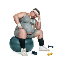 Funny overweight sports man sitting depressed on the fitness ball isolated on white background