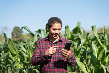 Asian farmer using smartphone in the corn field