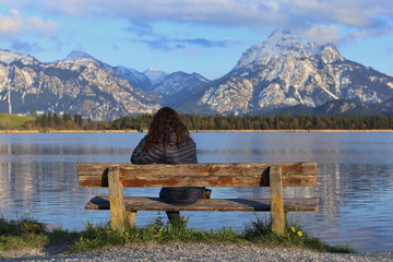 woman sitting at bench with beautiful view of the lake and mountains