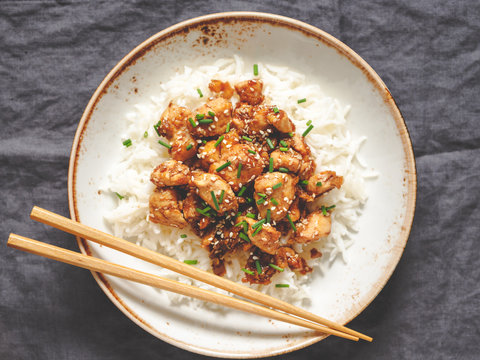 Top view on sesame chicken pieces with rice on a ceramic plate. Chinese traditional dish.