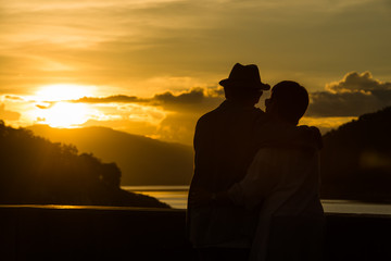 Image of sunset on orange and yellow horizon with a silhouette of a senior couple in natural surrounding