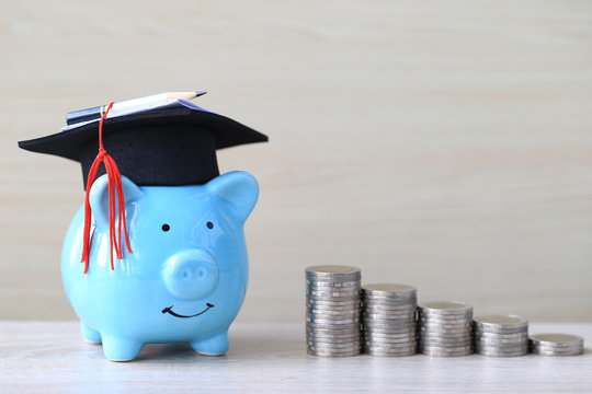 Graduation hat on blue piggy bank with stack of coins money on wooden background, Saving money for education concept