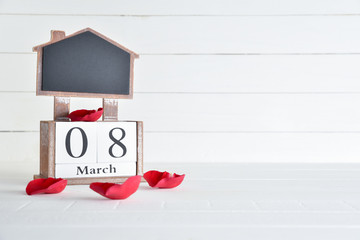 Womens day concept, happy womens day, international womens day. March 8 text wooden block calendar with red roses petal on white wooden background.