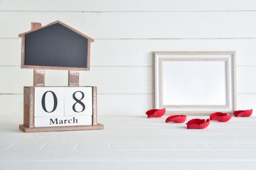 Womens day concept, happy womens day, international womens day. March 8 text wooden block calendar with picture frame and red roses petal on white wooden background.