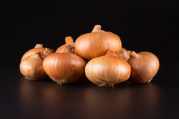 fresh beige onions on a black background, beautifully photographed, photo for poster, banner